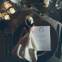 Detail shot of menu guest table setting, with gold charger, ivory napkin and stunning candle light, designed by Blooming Branch Creative and captured by Cheyenne Schultz Photography