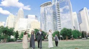 Romare Bearden Park uptown Charlotte wedding party walking with skyscraper background