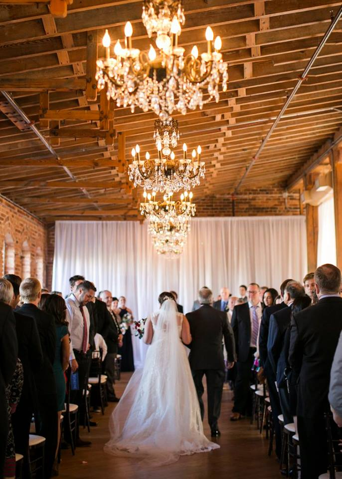 Bride walking down the aisle with chandeliers