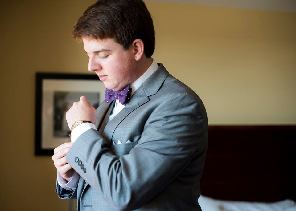 Magnificent Moments Weddings groom putting on his cuff links getting ready.