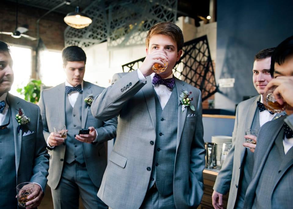 Groom and groomsmen having a drink before the wedding