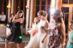 Owner of Magnificent Moments Weddings dancing with the bride at a wedding reception at Firethorne Country Club