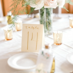 Gold table numbers and blush roses create a soft elegance for a summer wedding at Firethorne Country Club