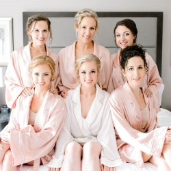 Bride poses with her bridesmaids in matching robes as they are pampered by Hello Gorgeous before their summer wedding coordinated by Magnificent Moments Weddings