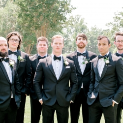 Groom poses with his groomsmen before his summer wedding at Firethorne Country Club