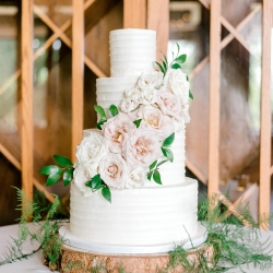 Four tier white cake created by Wow Factor shows off stunning blush flowers and wooden accents