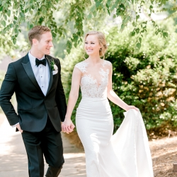 Bride and groom share a walk just before they exchange vows during their summer wedding coordinated by Magnificent Moments Weddings