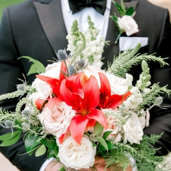 Groom shows off the stunning details of his bride's bouquets during their summer wedding at Firethorne Country Club just outside of Charlotte, North Carolina