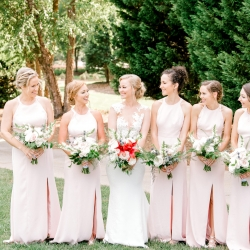 Bride poses with her bridesmaid wearing soft pink dresses and holding stunning white bouquets created by Lily Bee's florals