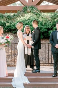 Bride and groom exchange vows during their wedding ceremony coordinated by Magnificent Moments Weddings
