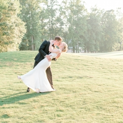 Groom dips his bride as they share a kiss during their wedding reception coordinated by Magnificent Moments Wedding at Firethorne Country Club