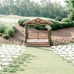 Arch draped with stunning greenery served as the perfect backdrop for a wedding ceremony coordinated by Magnificent Moments Weddings and captured by Alyssa Frost Photography