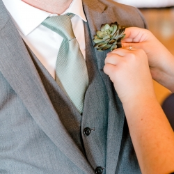 Groom dons his succulent boutonniere before his fall ceremony captured by Alyssa Frost Photography