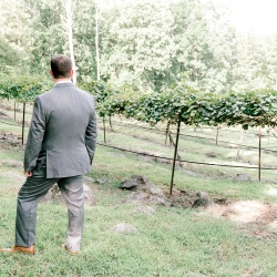 Groom stands among the vineyards in the North Carolina Mountains as he waits for his bride to complete their first look coordinated by Magnificent Moments Weddings