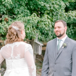 Groom reacts to seeing his bride during their first look before their fall wedding