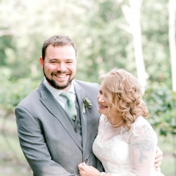 Bride and groom share a laugh as they prepare for their North Carolina mountain wedding that is captured by Alyssa Frost Photography
