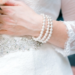Alyssa Frost Photography captures a detail shot of brides vintage pearl bracelet before her fall wedding at Stony Mountain Vineyards