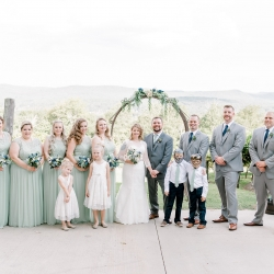 Bride and groom pose with their bridal party with scenic mountain views captured by Alyssa Frost Photography at Stony Mountain Vineyards