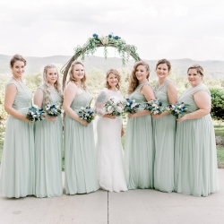 Bride poses with her bridesmaids who wear crisp teal dresses and hold simple floral bouquets