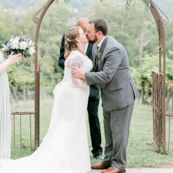 Alyssa Frost Photography captures the bride and grooms first kiss after exchanging their vows during their fall ceremony at Stony Mountain Vineyards