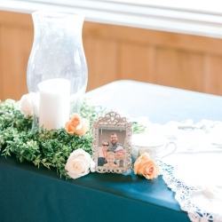 Detail shot of family pictures placed on a sweetheart table at a Stony Mountain vineyard wedding coordinated by Magnificent Moments Weddings