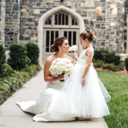 Bride with flower girl holding white bouquet designed by Lily Greenthumbs