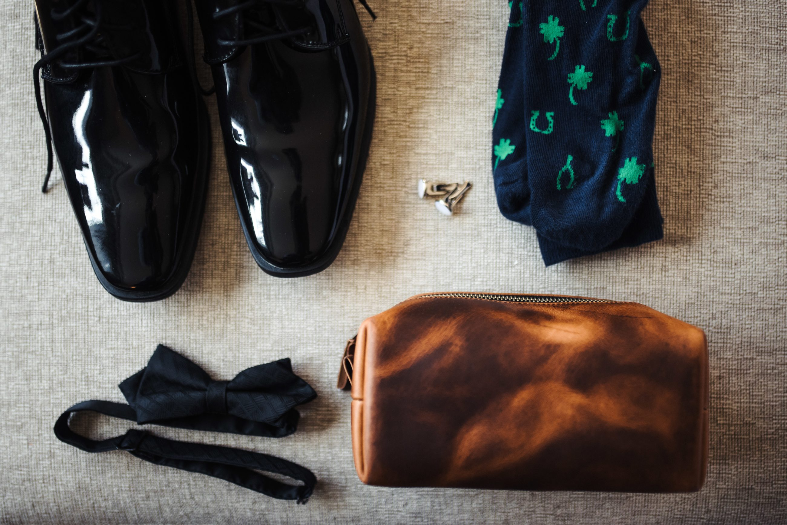 Detail show of grooms items including fun socks and black bow tie for Uptown Charlotte North Carolina Wedding