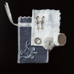 Wedding jewelry detail show showcasing delicate blue handkerchief capture by Anchor and Veil Photography