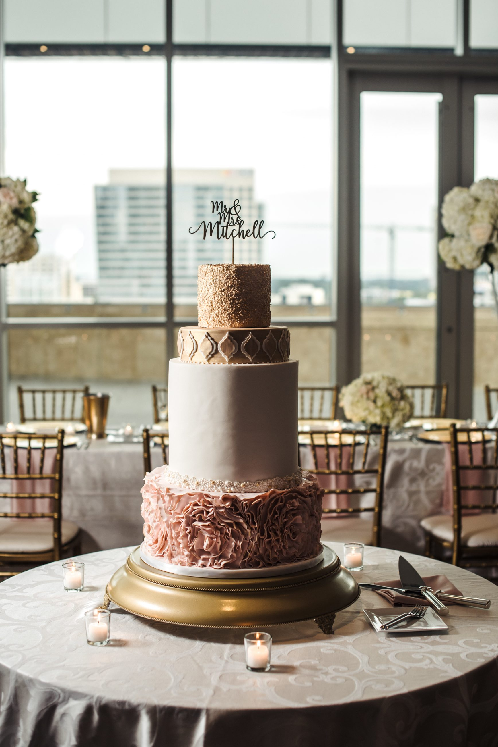 Four tier gold and blush cake with floral and geometric details created by Wow Factor Cakes