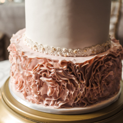 Detail show of four tier wedding cake with blush floral details created by Wow Factor Cakes on top of gold cake stand