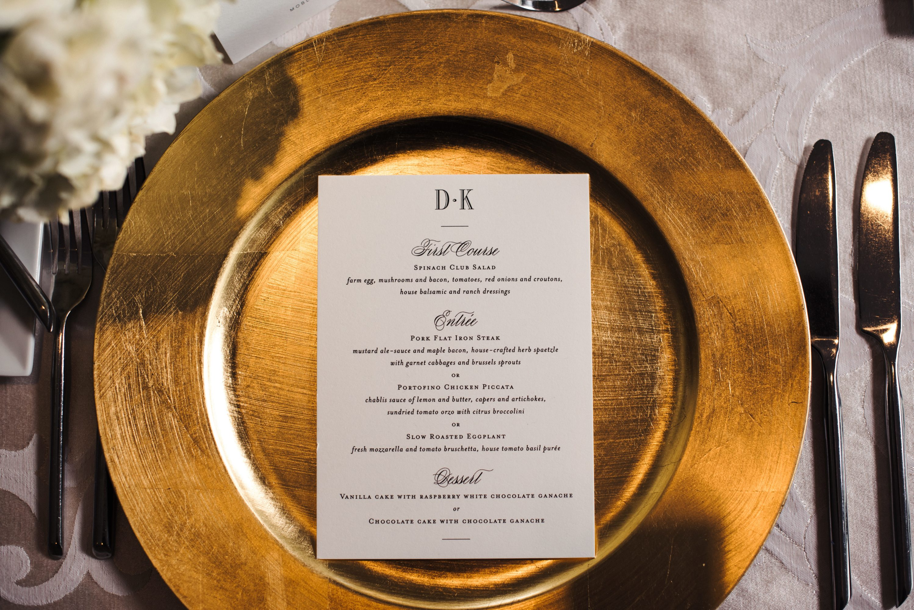 Wedding reception tablescape showcasing delicate ivory linens from CE Rental, gold chargers, and Ivory Menu cards