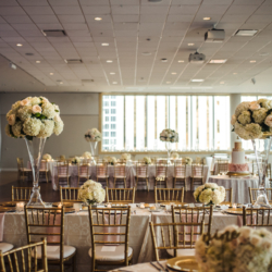 Uptown Charlotte wedding reception featuring tall floral centerpieces in glass vases featuring white hydrangeas and soft blush roses created by Lily Greenthumbs