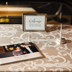 Guestbook table at Charlotte wedding with ivory linens rented from CE Rentals