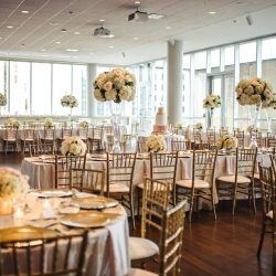 Wedding reception at Mint Museum Uptown, tables set with white linens from CE Rentals, gold chiavari chairs from Party Reflections