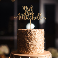 Four tier wedding cake with unique rose accents created by Wow Factor Cakes and topped with custom gold Mr. and Mrs. cake topper