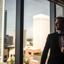 Groom getting ready in Uptown Charlotte set in front of cityscape background captured by Anchor and Veil Photography