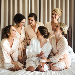 Bridal party getting ready photos in matching silk robes with lace sleeve detail hair and make up created by Beauty Asylum image captured by Anchor and Veil Photography
