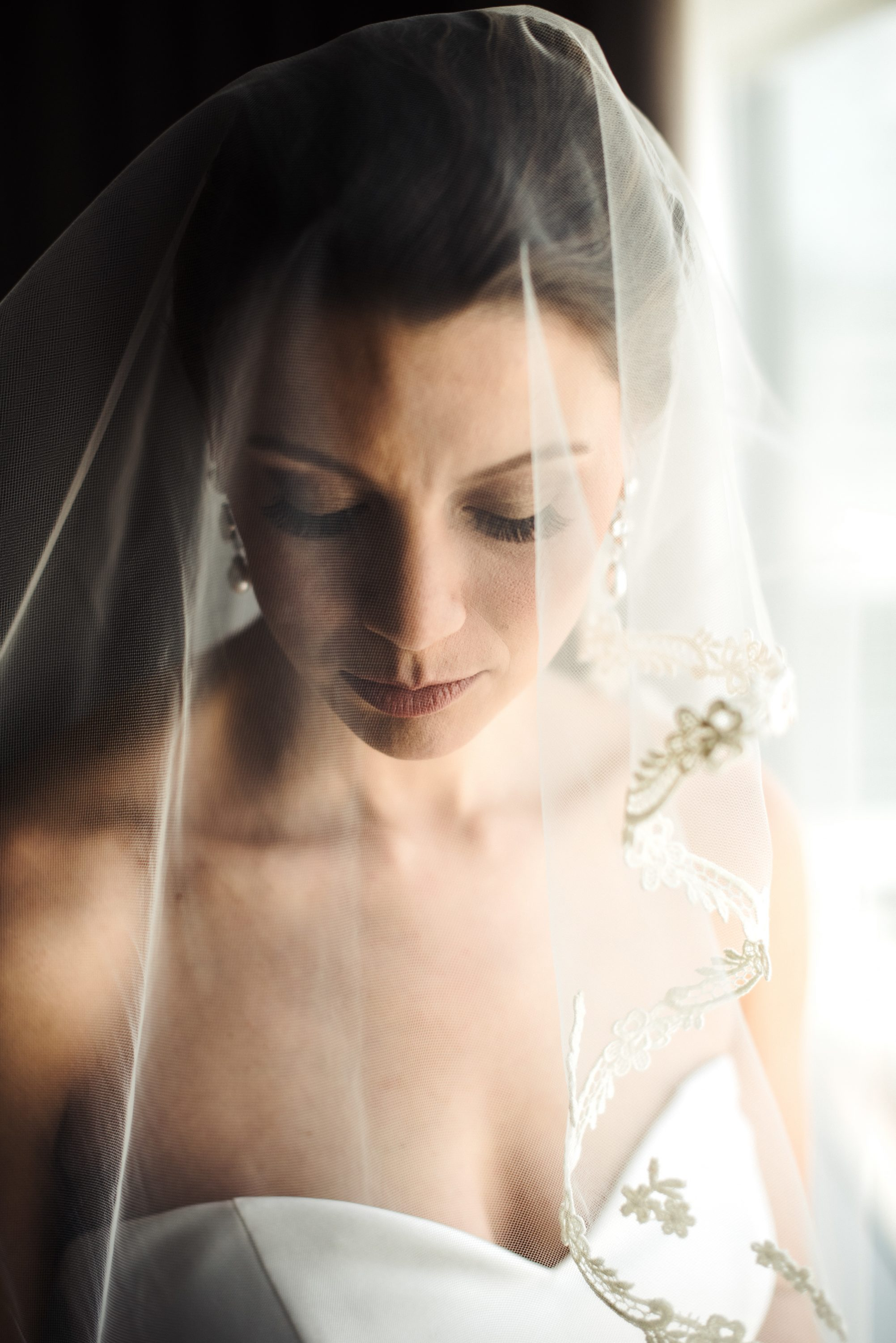 Bridal portrait under ivory veil with lace details showing off make up and hair created by Beauty Asylum