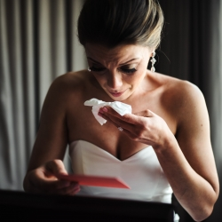 Bride's reaction to grooms gift getting ready for wedding at the Mint Museum Uptown