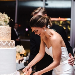 Bride and groom cake cutting gorgeous four tier cake with rose accents created by Wow Factor Cakes topped with custom gold topper captured by Anchor and Veil Photography