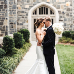 Bride and groom embrace as bride holds large bridal bouquet full of white hydrangeas and roses made by Lily Greenthumbs