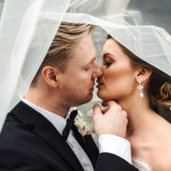 Bride and groom kiss under long ivory veil with lack details after their ceremony coordinated by Magnificent Moments Weddings