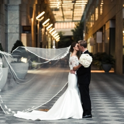 Bride and groom embrace after Charlotte North Carolina ceremony, bride wearing a dress from Hayden Olivia Bridal and holding a all white bouquet of hydrangeas and rose by Lily Greenthumbs