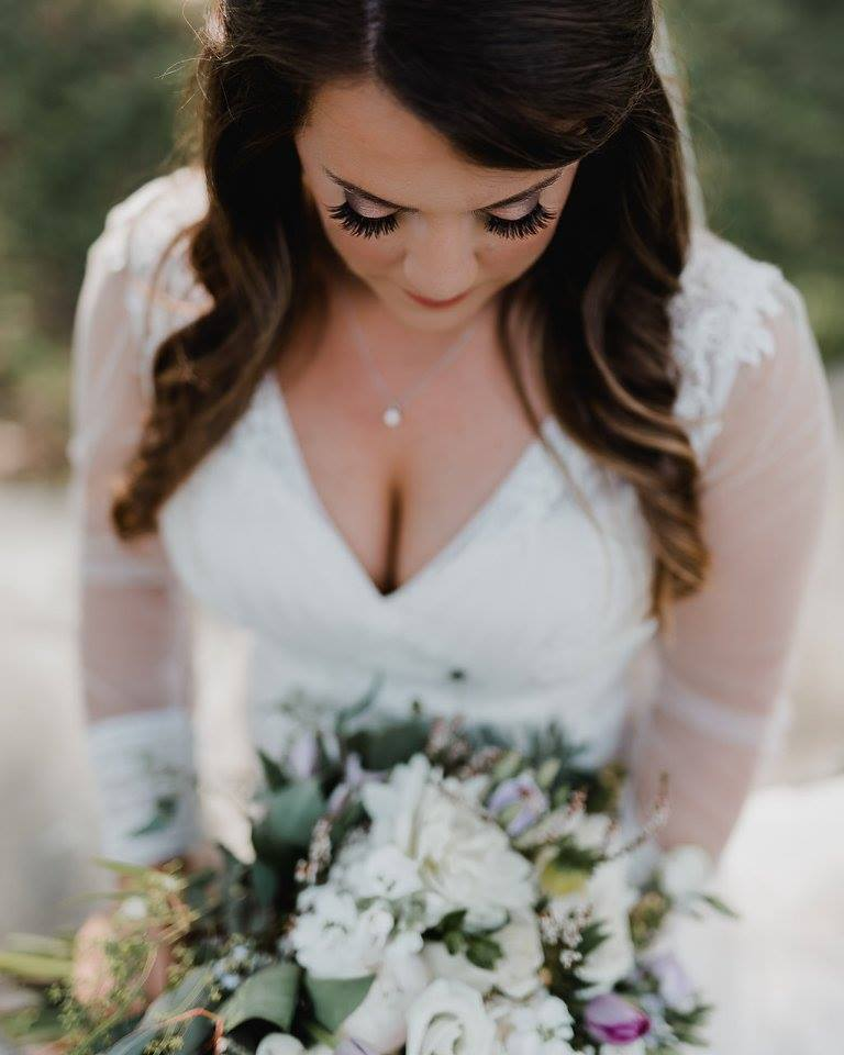 Bride looking down at her bouquet at Camellia Gardens in Monroe, NC