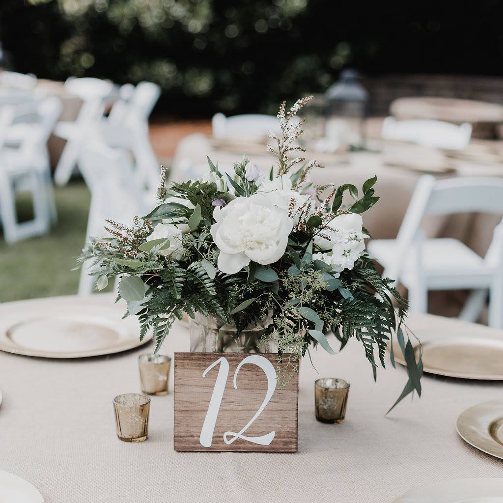 centerpieces with wood table number signs and gold mercury votive candles