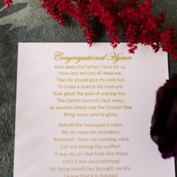 Hymn sheet given to guests for a winter wedding at Belk Chapel has stunning gold typography