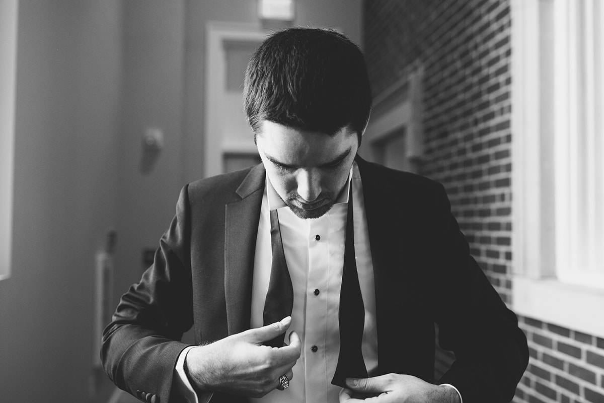 Groom prepares for winter uptown Charlotte wedding captured by Cameron Faye Photography