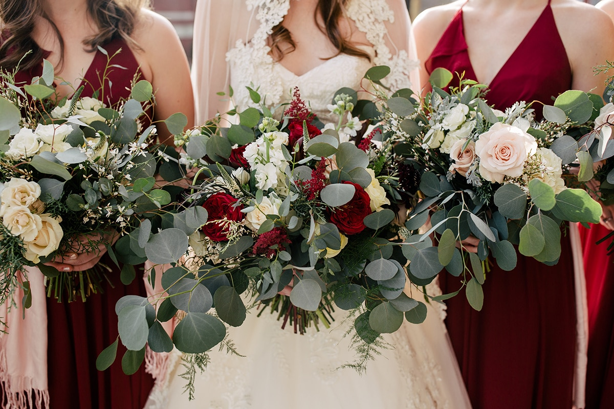 Bridal bouquet with deep red and blush flowers accented by lush greenery designed by Jimmy Blooms