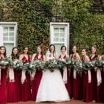 Bride stands with bridal party in amazingly deep red bridesmaids dresses all holding stunning hand tied bouquets by Jimmy Blooms