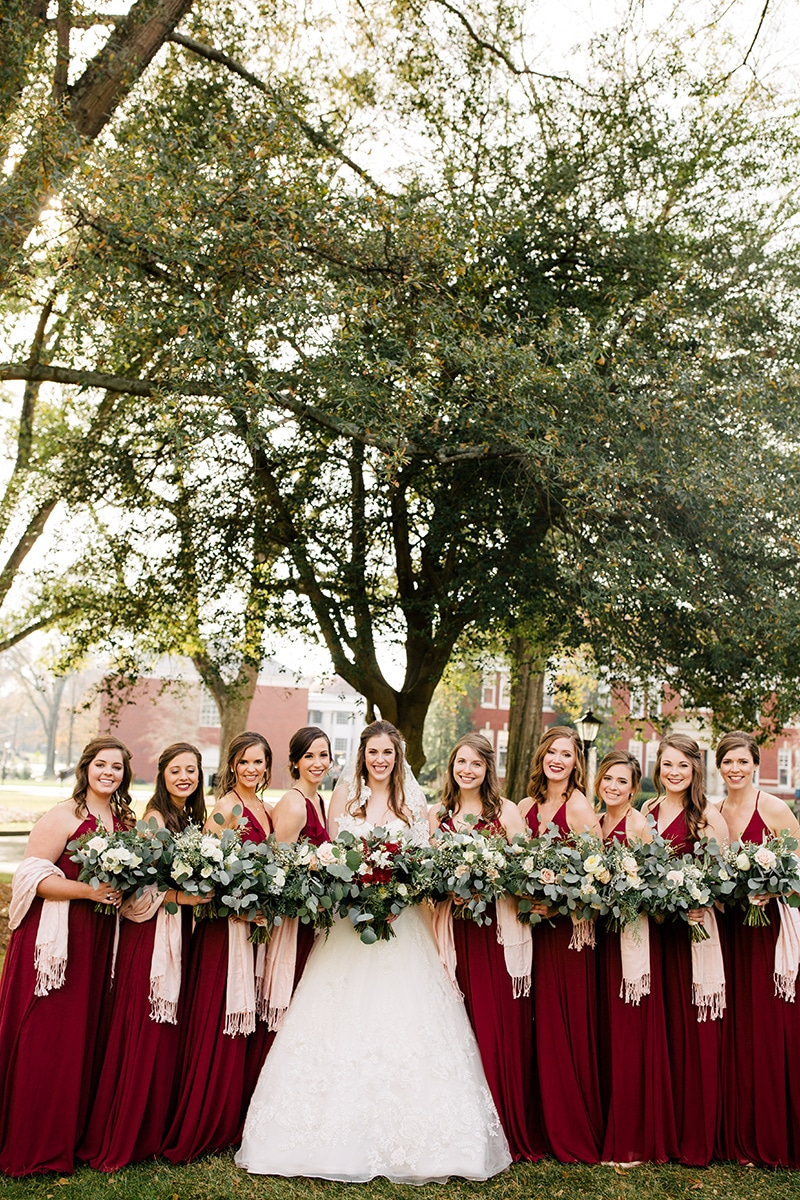 Bride stands with bridesmaids wearing deep red dresses and blush shawls captured by Cameron Faye Photography